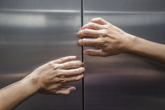 Woman hands try to stop doors of the closed elevator. Concept and idea royalty free stock images