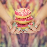 Woman hands with turquoise nail polish holding a plate with pink donuts. With pink pattern background royalty free stock images