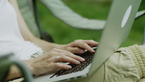 Woman hands typing. Close up of woman hands typing on a laptop outdoors stock footage