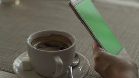 Woman hands typing on green screen mobile phone on background coffee cup. On saucer standing at table in cafe. Woman using green screen smartphone. Mockup stock footage
