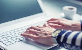 Woman hands typing on the keyboard of laptop, close-up of online. Working Royalty Free Stock Image