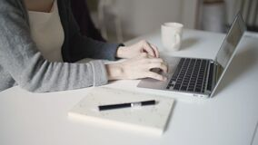 Woman hands typing on keyboard notebook sitting at table. Woman hands typing on keyboard notebook at table. Close up female hands using laptop for remote work stock video footage