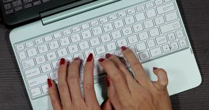 Woman hands typing on laptop computer. Top view of woman hands with nail polish working on laptop computer above desk. Shot in 4k resolution stock footage