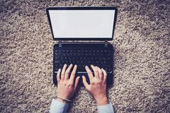 Laptop computer with white blank screen and hands typing on the keyboard. stock photo