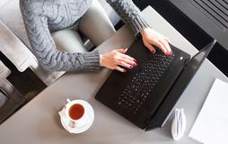 Woman hands typing on laptop. cup of tea. Up view. stock photography