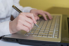 Woman hands typing on laptop keyboard. Holding pen in arm. Selective focus on hand. Can be used for technology, business and inter stock images