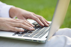 Woman hands typing on a laptop keyboard, outdoor Stock Image