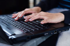 Woman hands typing on laptop Stock Photos