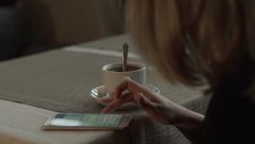 Woman hands typing message on screen mobile phone on background coffee cup. On saucer standing at table in cafe. Woman using smartphone during coffee break stock footage