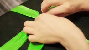 Woman hands untie green ribbon on black gift box. Lockdown shot of tender female hands unpacking present on wooden table. Personal perspective of lady stock video footage