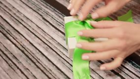 Woman hands untie green ribbon on gift box. Lockdown shot of tender female hands unpacking present on wooden table. Personal perspective of lady unpacking box stock video footage