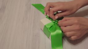Woman hands untie green ribbon on white gift box. Lockdown shot of tender female hands unpacking present on light wooden