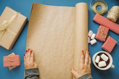 Woman hands unwrap the wrapping paper with space for text, hot c Stock Photos