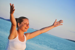 Woman with hands up expressing joy on the beach Royalty Free Stock Photography