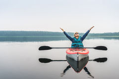 Woman with hands up extremely enjoying calmness of lake from the Stock Photos