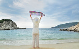 Woman with hands up holding a scarf on the beach Royalty Free Stock Image