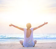Woman with hands up at sunrise beach Stock Images