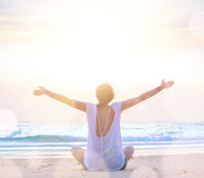 Woman with hands up at sunrise beach. Young caucasian woman embracing the sea at sunrise beach Stock Image