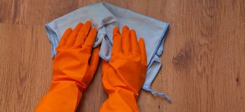 A woman hands Using blue rags wipe the wooden floor.  Royalty Free Stock Photos