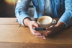 Woman hands using on her smart phone sitting at wooden table in a coffee sho Stock Photo