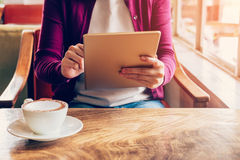 Woman hands using and holding  computer tablet in coffee shop Stock Photo