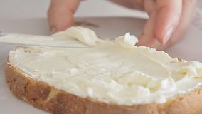 Woman hands spreading cheese on bread slice. Woman hands using kitchen knife and spreading cheese on bread slice video footage filmed from low angle in slow stock footage