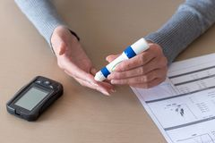 Woman hands using lancet on finger to check blood sugar level. Close-up of woman hands using lancet on finger to check blood sugar level by Glucose meter. Health Stock Image