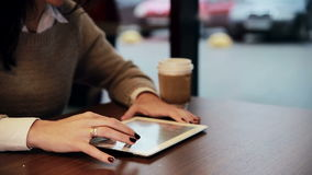 Woman hands using tablet touchscreen in cafe. Close up woman hands using digital tablet touchscreen  in cafe stock footage