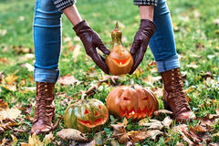 Woman hands in leather gloves holds a Halloween pumpkin outdoor in the autumn park Royalty Free Stock Photos