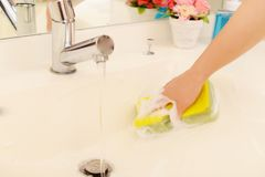 Woman hands cleaning washroom. Woman hands wash the washbowl Stock Images