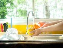 Woman hands washing fresh orange. Image of woman washing fresh orange Stock Photo