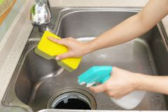 Woman wash the kitchen sink. Woman hands washing the kitchen sink royalty free stock images