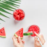 Woman hands with watermelon smoothie drink glass. Creative scandinavian style flat lay top view of fresh watermelon slices smoothie drink in glass woman hands on stock images