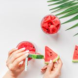 Woman hands with watermelon smoothie drink glass. Creative scandinavian style flat lay top view of fresh watermelon slices smoothie drink in glass woman hands on stock photography