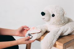 Woman hands and white heart gingerbread on paw of old bear toy. On wooden chair on grey background stock photography