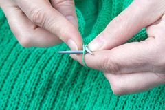 Woman hands who knits a green sweater. Close up view of a elderly woman hands who knits a green sweater Stock Images