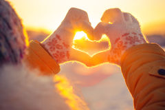 Woman hands in winter gloves Heart symbol shaped. Lifestyle and Feelings concept with sunset light nature on background royalty free stock image