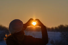 Woman hands in winter gloves. Heart symbol shaped, lifestyle and. Feelings concept with sunset light nature on background Royalty Free Stock Photo