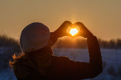 Woman hands in winter gloves. Heart symbol shaped, lifestyle and. Feelings concept with sunset light nature on background Stock Photos