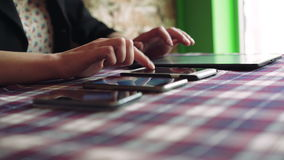 Woman hands working with a tablet near three phones on a table in cafe 4k stock video