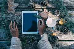Woman hands working on a tablet in a wooden table with coffee an Stock Photos