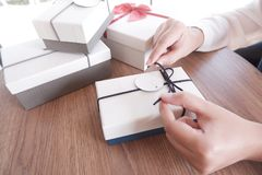 Woman hands wrapping gift box, unwrap or open present stock image