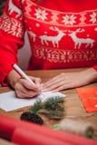 Woman hands writing on christmas postcard Royalty Free Stock Photo