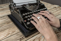 Woman Hands writing on old typewriter. Old typewriter and a blank sheet of paper, retouching author writer. Blue wooden table dry flowers. Top view. The creative Royalty Free Stock Photo