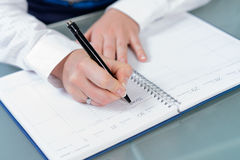 Woman hands writing plans with a pen at notebook Stock Photo