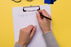 Woman hands writing a shopping list on a yellow background. Free space. Copy space. Flatlay stock photos