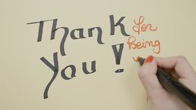Woman hands writing thank you for being you on a blank greeting card using black and red marker and drawing a smiley face -. Woman hands writing thank you for stock footage