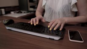Woman hands with yellow nails typing on the keyboard. Mobile phone is on the wooden table. Woman hands with yellow nails typing on the keyboard. Mobile phone is stock video
