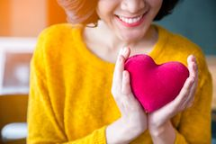 Woman hands in yellow sweather holding pink heart. royalty free stock photography
