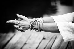 Woman hands in yoga symbolic gesture mudra bw. Woman hands in yoga symbolic gesture mudra wearing lot of bracelets and rings outdoor closeup by the lake summer royalty free stock images
